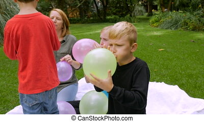 A mother and her three children blow up balloons together - slowmo