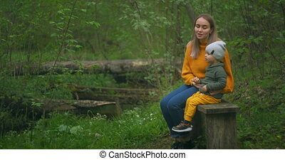 A mother and her young son sit on a bench in the Park and talk. The mother explains to the little boy answering inquisitive questions