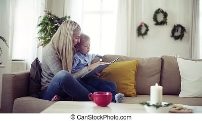 A mother and small boy sitting on a sofa at home at...