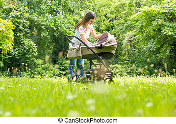 A mother checkin her baby in a stroller in the park