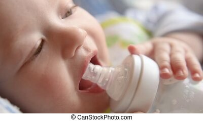 A mother feeds her baby milk from a bottle. Close-up
