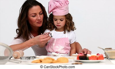 A mother helping her daughter to bake in the kitchen