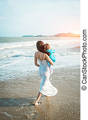 A mother holds her little daughter in her arms on the beach and go to sea.