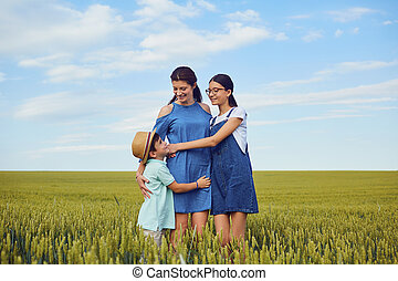 A mother hugs with children in a field of wheat in nature.