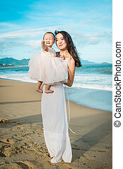 A mother in white dress holds her little daughter in her arms on the beach.