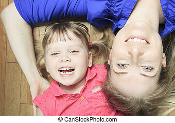 A mother lay in the living room floor with daughter