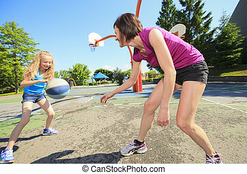 A mother play basketball with his daughter