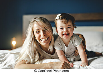 Mother Playing With Baby Daughter In Bedroom At Home