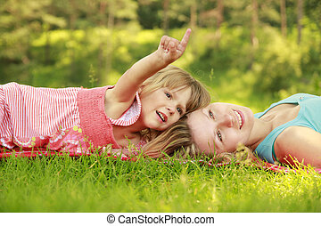 mother playing with her ??little daughter on the grass