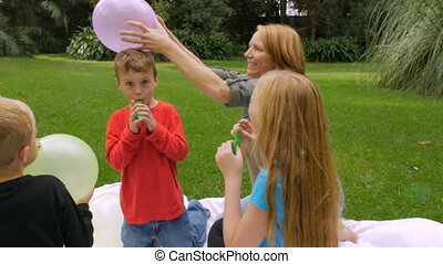 A mother rubs a balloon on her son's head to create static...