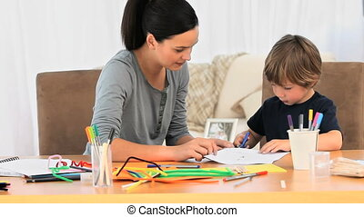 A mother smiling  while her son is drawing