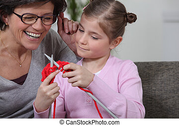 A mother teaching her daughter how to knit.