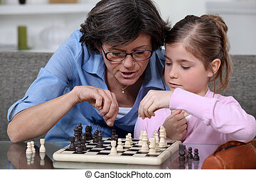 A mother teaching her daughter how to play chess.