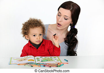 A mother teaching her son how to draw.