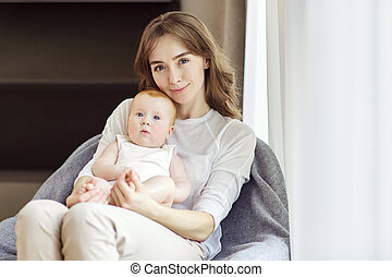 A mother with a baby in her arms sitting on a chair in front of