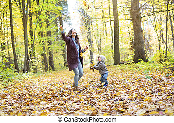 Mother with son in forest in autumn