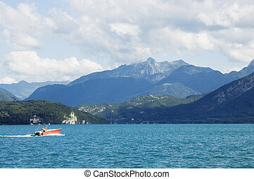A motor boat crosses the lake Annecy - A red motor boat...