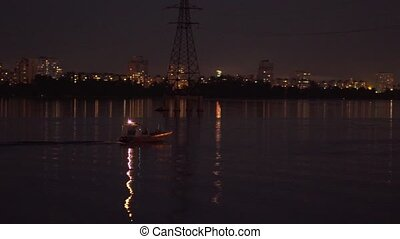 A motor boat drifts on the river at night - A motor boat ...