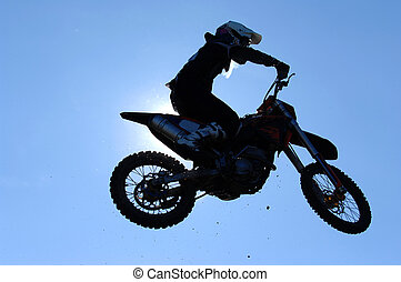 A motorcross rider in the air during a race.