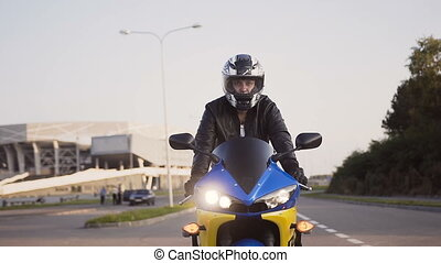 A motorcyclist rides a city on his yellow-blue motorcycle in a helmet and a leather jacket