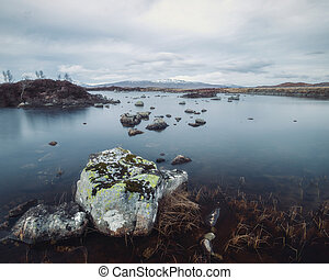 A mountain lake in the Scottish Highlands with stones in the water