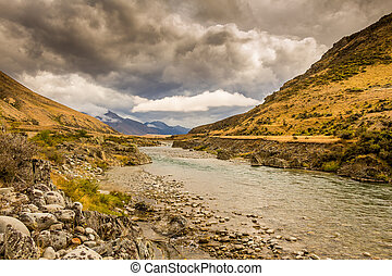 A mountain landscape and river on a cloudy day in New Zealand near Omarama