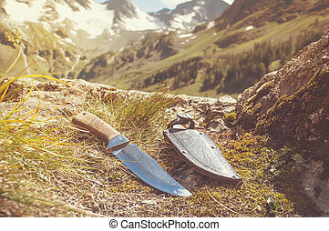 A mountain man knife and leather sheath displayed