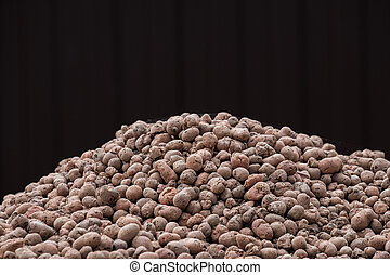 A mountain of clay expanded clay granules on a dark brown background.