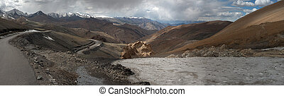 A mountain road passing through the pass and circles descending the ridges of ridges, the Himalayas, Northern India, a photo panorama.