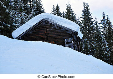 A mountain wooden hut covered with fresh snow