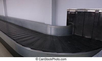 A moving baggage carousel or conveyor belt closeup.