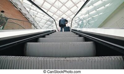 A moving escalator inside an airport. A man standing with a...