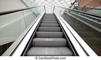 A moving escalator inside an airport. Mid shot