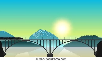 A moving freight train on the bridge in the background of a mountain landscape at dawn
