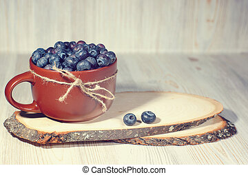 A mug full of blueberries stands on the spiers of a tree, a rustic style