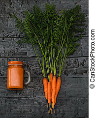 A mug of carrot smoothie and a bunch of carrots on a rustic table. The view from the top. Flat lay.