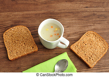 A mug of vegetable soup displayed with bread, a green napkin and a spoon on a wooden background