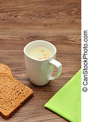 A mug of vegetable soup displayed with bread and a green napkin on a wooden background