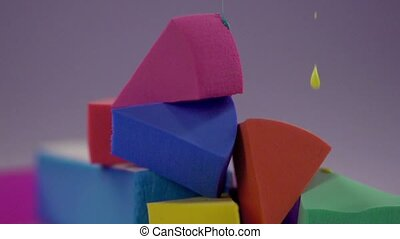 A multicolored paint drips onto the pyramid from the sponge for make-up.