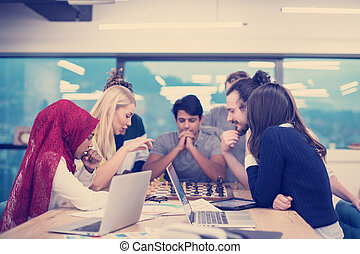 multiethnic group of business people playing chess