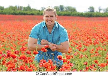 A muscular guy on the poppy field
