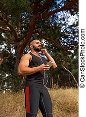 A muscular sportsman on a blurred background. A sportive jogger listening to some music before running. Sports, music concept.