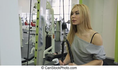 A muscular woman athlete performs triceps strain on hand in the gym.
