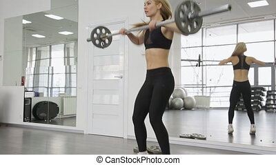 A muscular woman athlete using the barbell with weights, trains on the squats. buttocks, ass in the gym.