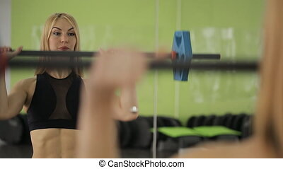 A muscular woman athlete using the barbell with weights, trains on the shoulders and triceps in the gym.
