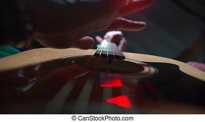 A music teacher plays an acoustic guitar.