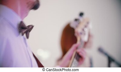 A musical band playing a song - a man playing bass guitar