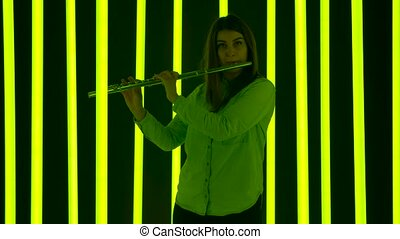 A musical concert of classical music performed by a professional female flutist. Young woman plays music in a dark studio against the backdrop of bright neon lights. Silhouette. Slow motion