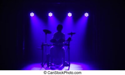 A musician drummer who plays a musical instrument in a dark ...