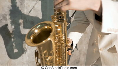 A musician in a white suit plays the saxophone. He performs in a nightclub, against a gray background. close-up